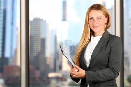 Portrait of business woman standing  near window