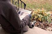 žena sedí na schodech ve vlněném kabátě a čtenářský deník s hlavičkou nemovitostí