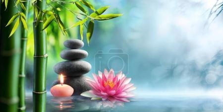 Photo pour Spa - Thérapie alternative naturelle avec des pierres de massage et nénuphar dans l'eau - image libre de droit