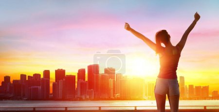 Jogging, Fitness And Success - Girl With Arms Raised And Cityscape At Sunset