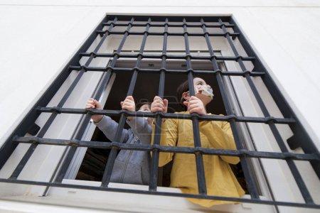 Dos niños miran tristemente al aire libre a través de una ventana de hierro forjado. Impacto en los niños del confinamiento de Covid-19