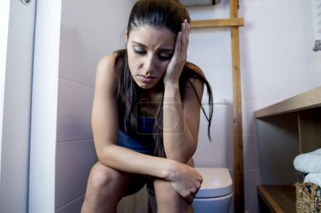 young sad and depressed bulimic woman feeling sick sitting in toilet WC looking desperate and ill