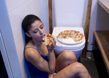 bulimic woman feeling sick guilty sitting at the floor of the toilet leaning on WC eating pizza