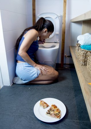 Photo for Young sad and depressed bulimic woman feeling sick guilty vomiting and throwing up kneeling on floor of toilet WC guilty after eating pizza in nutrition disorder bulimia and anorexia concept - Royalty Free Image