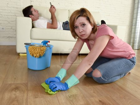 husband resting on couch while wife cleaning doing housework in chauvinism concept