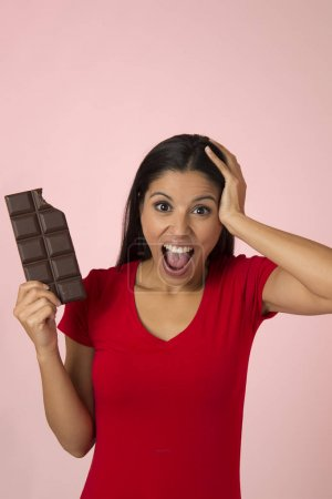 young attractive and happy hispanic woman in red top smiling excited eating chocolate bar isolated on pink background