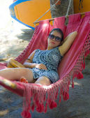 young pretty happy Asian Chinese woman lying lazy on beach hammock sun bed relaxed and cheerful in Summer holiday trip enjoying vacation