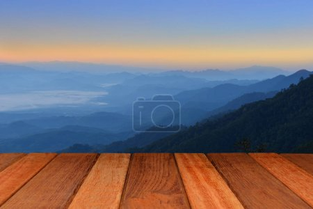 Empty wood table top with mountain background at sunrise