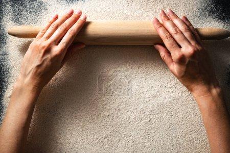 Photo pour Aplatissement des mains de la femme et rouleau avec farine. Concept de fabrication de pain. Une alimentation saine sans gluten. Table des matières. - image libre de droit