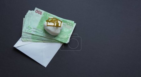 Photo pour Billets en euros dans une enveloppe blanche et figure de la maison sur fond noir. Vue aérienne à plat. Espace de copie. Concept de charge hypothécaire . - image libre de droit