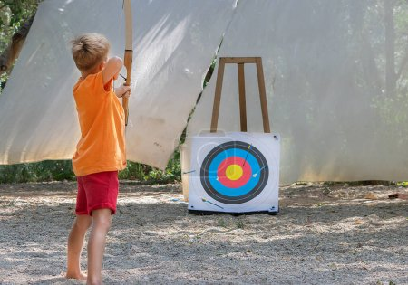 Photo for Small boy shooting with bow - Royalty Free Image