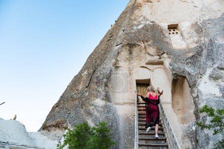 Photo pour Une femme monte de vieux escaliers dans une ancienne grotte volcanique en Cappadoce, Turquie. - image libre de droit