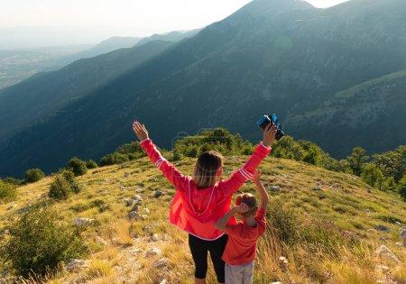 Photo pour Mère et fils actifs admirant les montagnes, mains levées - image libre de droit