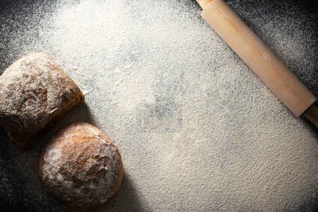 Photo for Flat lay of freshly baked bread and rolling pin on flour. Gluten free healthy diet. Bread making concept. Copy space. - Royalty Free Image