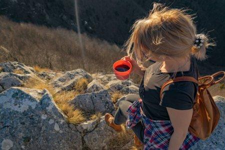 Photo pour Jeune femme randonneuse relaxante avec une tasse de café au bord de la falaise profitant d'une vue panoramique sur les montagnes et le coucher du soleil. Vue aérienne. Espace de copie. Concept de randonneur . - image libre de droit