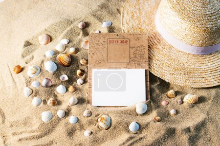 Photo for Blank calendar mockup with straw hat and sea shells on sand. Overhead view, copy space. Summertime concept. - Royalty Free Image