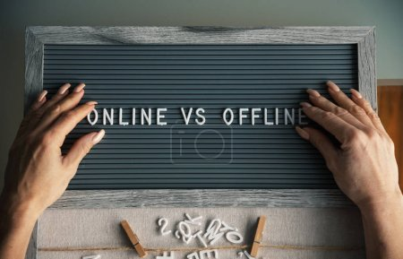 """Photo for Woman making text """"Online vs offline"""" with letters on typesetting board - Royalty Free Image"""