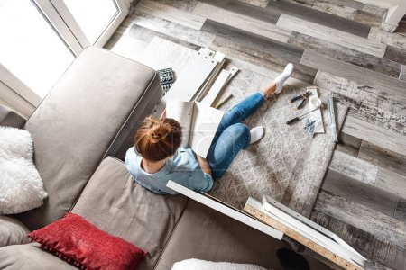 Photo for Concentrated young woman reading the instructions to assemble furniture at home in the living room - Royalty Free Image