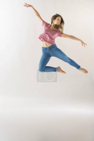Foto de Bailarín de ballet clásico femenino saltando en el aire usando ropa casual, estudio tiro. - Imagen libre de derechos