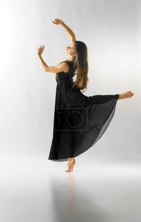 Photo pour Danseur de ballet féminin sur une jambe avec les bras en avant, studio tourné. - image libre de droit
