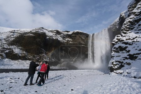 Tourists viewing snow covered landscape