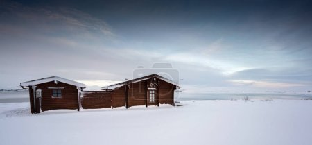 Log cabin retreat in deep snow covered landscape