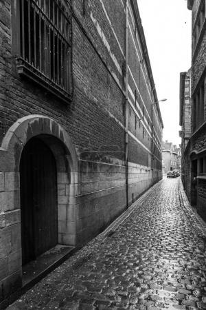 Photo pour Vue le long d'une rue étroite de bâtiments et de galets, noir et blanc, Belgique - image libre de droit