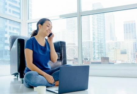 Woman with laptop using mobile phone