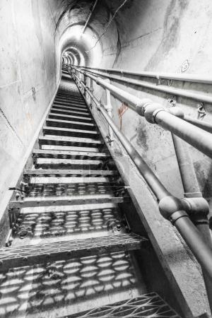 Photo for View of steps inside empty industrial concrete tunnel, diminishing perspective. - Royalty Free Image