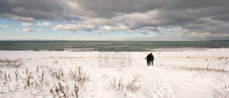 Photo pour Deux personnes marchant sur la neige couverte vue arrière de la plage (Ontario) Canada - image libre de droit