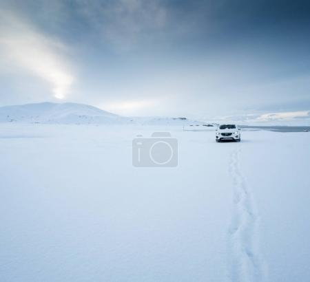 Stationary car covered in deep layer of snow
