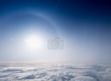 Sun halo, sun glare and blue sky above cloudscape