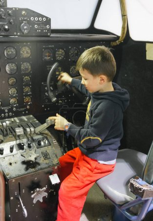 Young boy in cockpit of stationary aeroplane