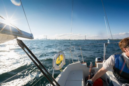 Photo for Man on sailboat in summer on sunny day, Toronto, Ontario, Canada - Royalty Free Image