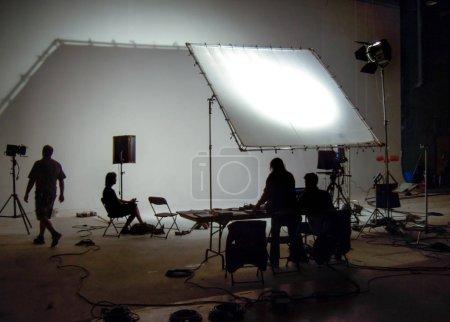 Foto de En el interior, silueta del grupo de personas en la sesión de fotos con equipos de iluminación. - Imagen libre de derechos