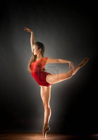Foto de Bailarín de ballet clásico femenino sobre una pierna mirando recto hacia adelante, estudio de disparo - Imagen libre de derechos