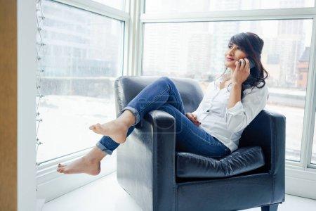 Photo pour Jeune femme assise à l'intérieur, dans une chaise à l'aide de téléphone portable, jour - image libre de droit