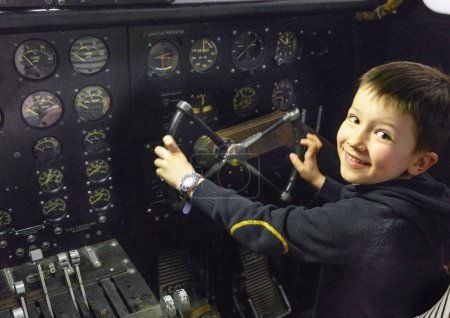 Young boy smiling, steering wheel in cockpit