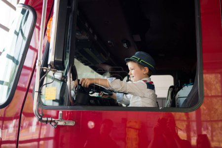 Photo for Young boy in driving seat of truck, holding steering wheel, smiling - Royalty Free Image