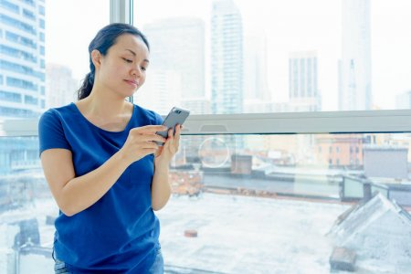 Photo for Woman standing indoors by window, urban scene, using mobile phone - Royalty Free Image