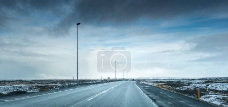 Bleak snowy landscape, road and stormy sky