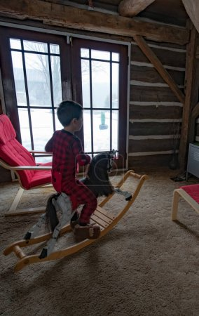 Boy sat on rocking horse indoors
