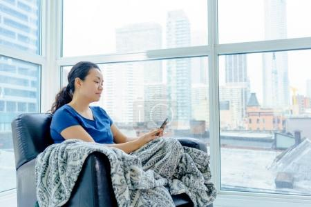 Photo for Woman sitting in chair by window, using mobile phone - Royalty Free Image