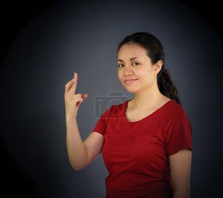 Photo pour Portrait de femme regardant la caméra avec les doigts croisés, studio shot - image libre de droit