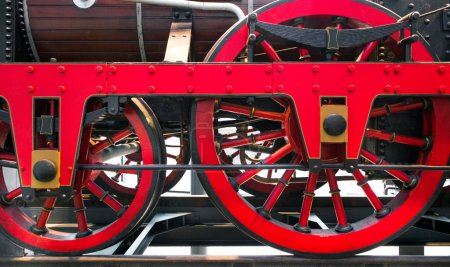 Close up of red metal wheels on old fashioned steam powered train