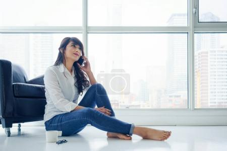 Young woman sitting on floor next to window using mobile phone
