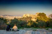 Rear view of a couple sightseeing The Acropolis - Athens, Greece from a distance, Europe