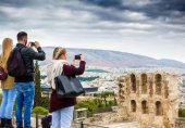 Tourist capturing Theater of Herodes Atticus and Odeon Building on mobile phone, Athens, Greece