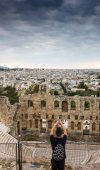 Tourist photographing Odeon of Herodes Atticus and Cityscape using mobile camera, Athens, Greece