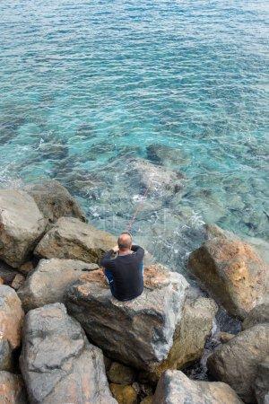 Photo pour Homme pêche à partir d'une côte rocheuse - image libre de droit